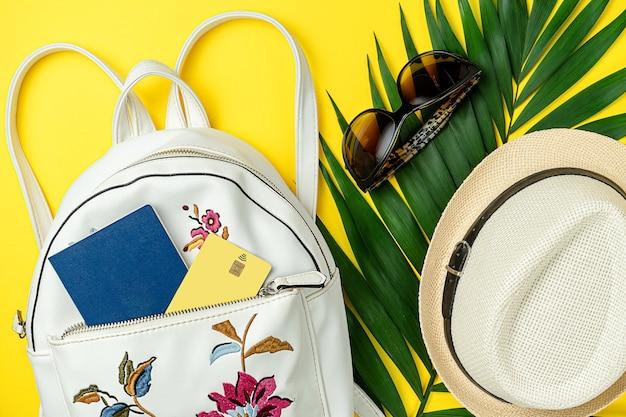 Concetto di viaggio estivo. accessori, zaino con passaporto e carta di credito su vivace superficie gialla. vista dall'alto