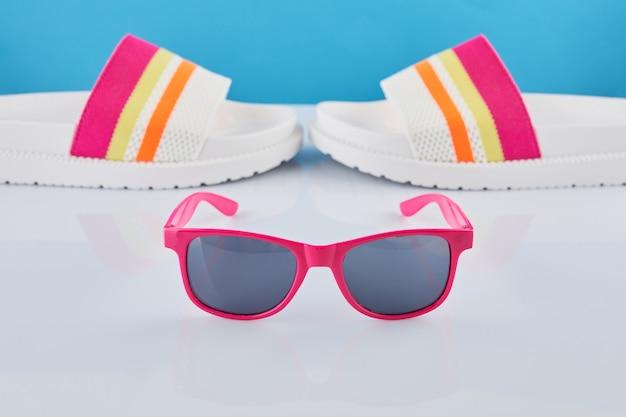 Concetto di viaggio estivo. infradito o pantofole e occhiali da sole su uno sfondo pastello.