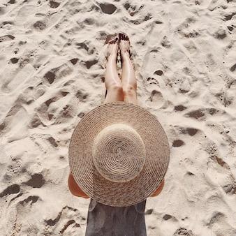 Concetto di moda di viaggio estivo. bella giovane donna abbronzata con un cappello di paglia è sdraiato e rilassante sulla spiaggia tropicale con sabbia bianca che mostra le gambe