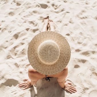 Concetto di moda di viaggio estivo. bella giovane donna abbronzata con un cappello di paglia è sdraiato e rilassante sulla spiaggia tropicale con sabbia bianca Foto Premium