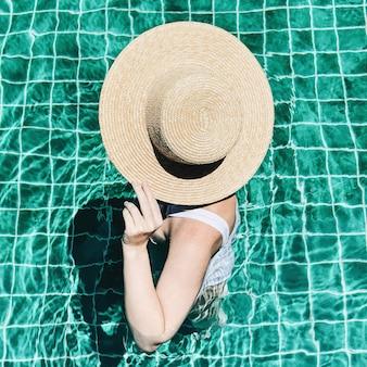 Moda di viaggio estivo e concetto di vacanza. bella giovane donna abbronzata con un cappello di paglia e un costume da bagno bianco è in piedi in piscina