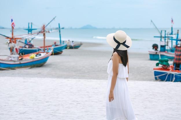Concetto di vacanza di viaggio di estate, donna asiatica del viaggiatore felice con vestito e cappello di paglia che cammina sulla spiaggia del mare a hua hin, tailandia