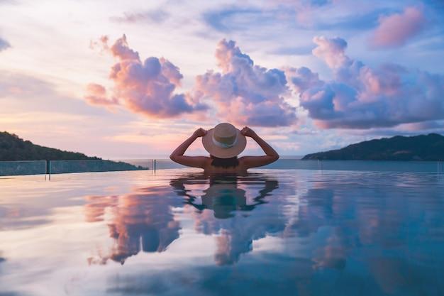 Il concetto di vacanza di viaggio estivo, la donna asiatica del viaggiatore felice con il cappello e il bikini si rilassa nel resort di lusso dell'hotel della piscina a sfioro con la spiaggia del mare al tramonto a phuket, tailandia