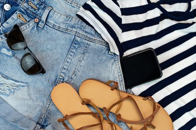 Accessori da spiaggia per viaggiatori estivi. concetto di viaggio o di vacanza. disposizione. jean e sandali da spiaggia e occhiali da sole