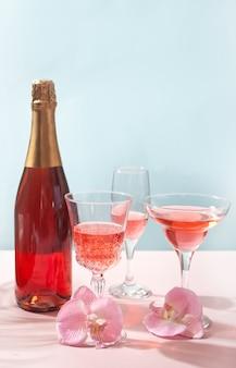 Champagne di vino da cocktail rosa tropicale estivo in bicchieri diversi con fiori di orchidea rosa decorati con bottiglia.