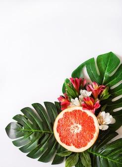 Sfondo a tema tropicale estivo o modello con uno spazio per un testo, vari frutti, foglie verdi e fiori. sfondo luminoso estivo