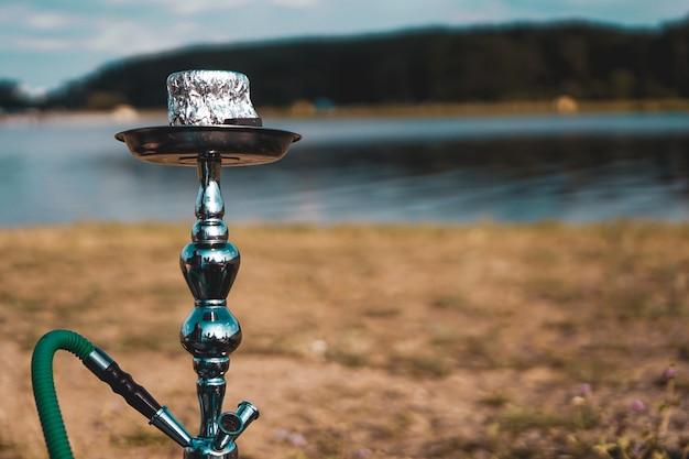 Vacanze estive, attività. ambiente, viaggi e concetto di fumo di narghilè. la ciotola del narghilè si trova nella natura vicino al fiume da vicino