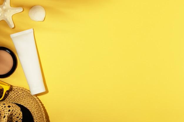 Sfondo vacanze estive con accessori. cappello di paglia, conchiglia, stella marina e occhiali da sole. tubo senza marchio per creme solari o lozioni idratanti, prodotti cosmetici. copia spazio su sfondo giallo.