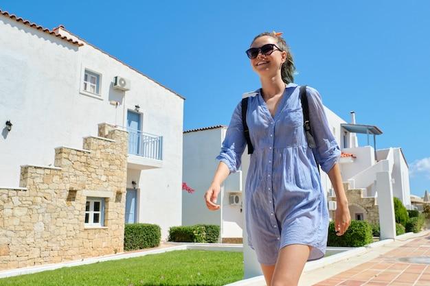 Vacanze estive, bella ragazza adolescente che cammina all'hotel resort sea spa. paesaggistico, sfondo di case d'albergo. tempo libero, svago, turismo, stile di vita di giovani, adolescenti