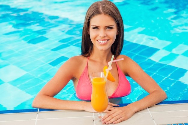 Vacanze estive. bella giovane donna in bikini che tiene un cocktail e sorride mentre sta in piedi in piscina