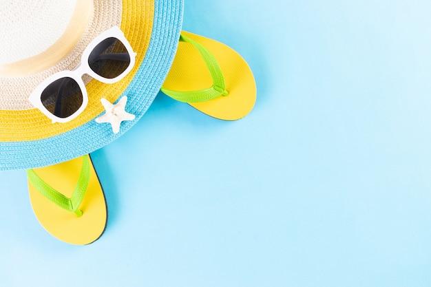 Concetto di estate o vacanze. cappello da spiaggia, occhiali da sole e infradito su sfondo azzurro. copia spazio