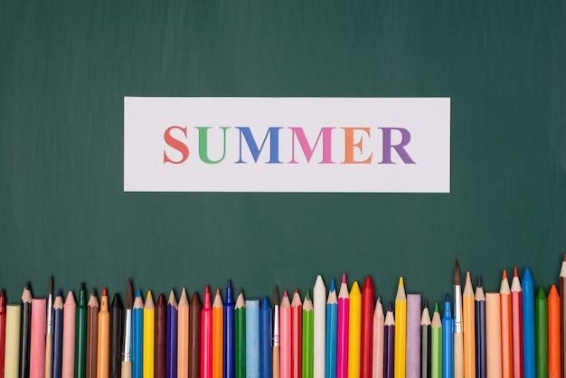 Concetto di vacanza estiva. in alto sopra la foto vista dall'alto di carta estiva e pastelli colorati isolati su greenboard