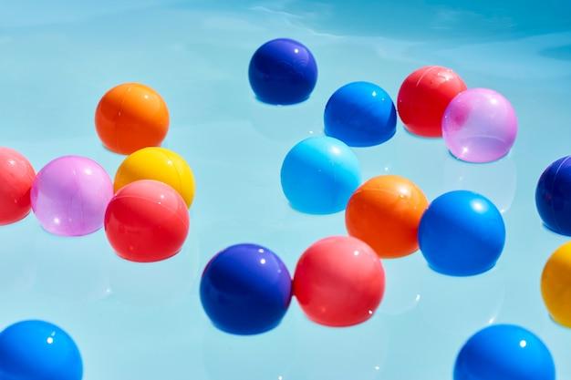 Concetto di vacanza estiva con palla colorata nell'acqua della piscina, primo piano
