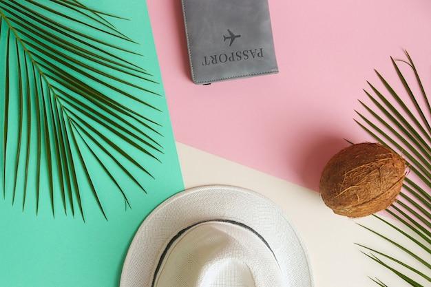 Vacanze estive piatte foglie di palma laici cappello estivo cocco e passaporto su tavolo beige verde rosa