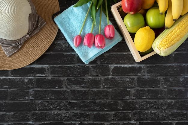 Tulipano di frutta di vacanze estive e cappello da sole nella vista superiore piana del fondo del muro di mattoni con lo spazio della copia