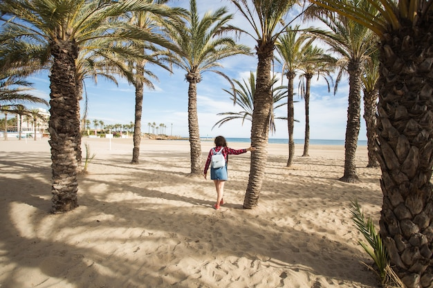 Vacanze estive, vacanze e concetto di viaggio - bella giovane donna sotto i rami delle palme in riva al mare.