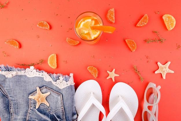 Vacanze estive cocktail di frutta arancione detox acqua vicino a infradito bianche pantaloncini e occhiali da sole