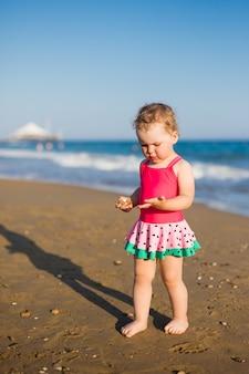 Vacanze estive e concetto di viaggio - ritratto di bambina in costume da bagno che raccoglie ciottoli in spiaggia
