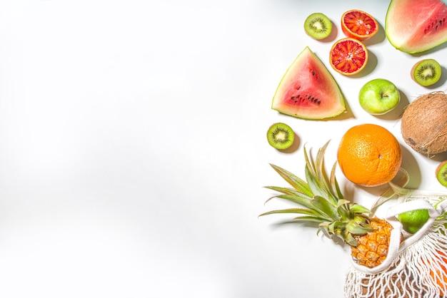 Estate vegetariana e concetto di acquisto sostenibile, borsa della spesa piena di frutta fresca tropicale, sul tavolo bianco