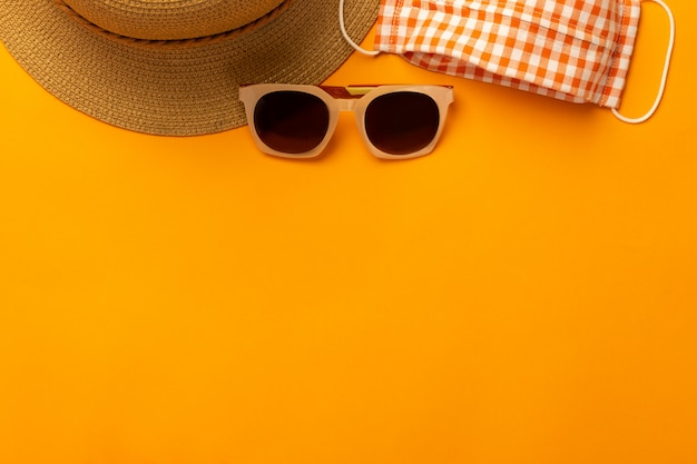 Parete estiva con accessori da spiaggia - cappello di paglia, occhiali da sole, maschera per prevenire covid-19 sulla vibrante parete arancione vista dall'alto con spazio di copia