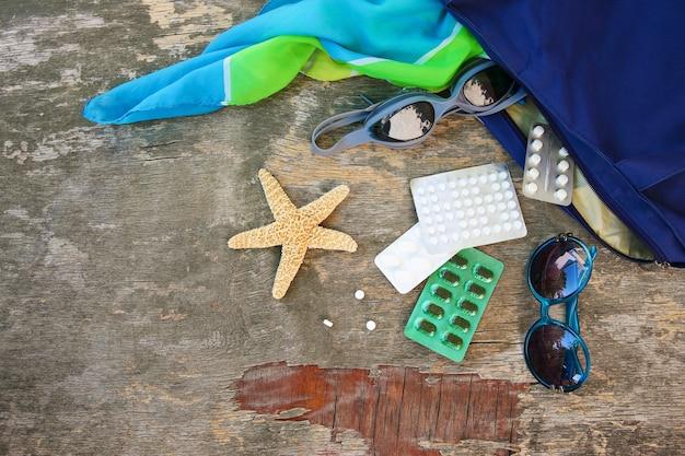 Accessori da spiaggia da donna estivi per la tua vacanza al mare e pillola su fondo in legno vecchio. concetto di farmaco richiesto in viaggio. vista dall'alto.