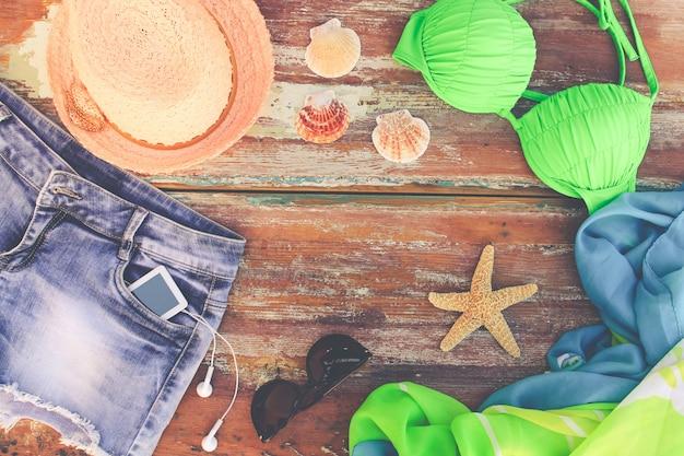 Abbigliamento e accessori estivi da donna: cappello, costume da bagno, shorts in denim, pareo, occhiali da sole, conchiglie. vista dall'alto.