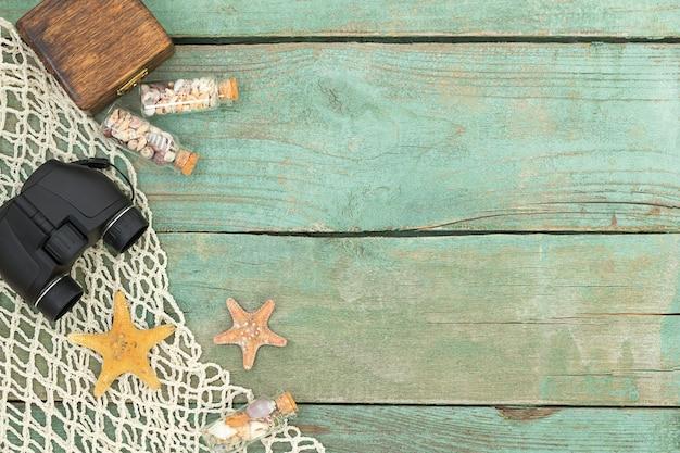 Fondo di viaggio di mare di legno di estate con le piccole bottiglie delle stelle marine con il binocolo delle conchiglie e la rete del mare