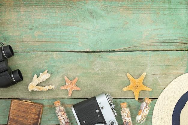 Fondo del mare di viaggio in legno estivo con fotocamera bunoculares cappello stelle marine e bottiglie con conchiglie