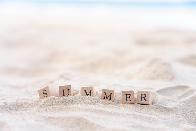 La parola dell'estate scritta sul blocco di legno ha messo sopra la spiaggia di sabbia.