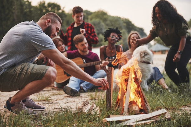Felicità estiva. un gruppo di persone fa un picnic sulla spiaggia. gli amici si divertono durante il fine settimana.