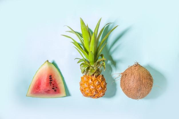Vacanze estive e concetto di vacanza, sfondo luminoso giallo blu moderno con frutta tropicale fresca - cocco, ananas, anguria
