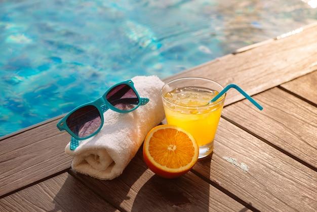 Il cappello e gli occhiali da sole estivi per il succo d'arancia si rilassano vicino alla piscina.