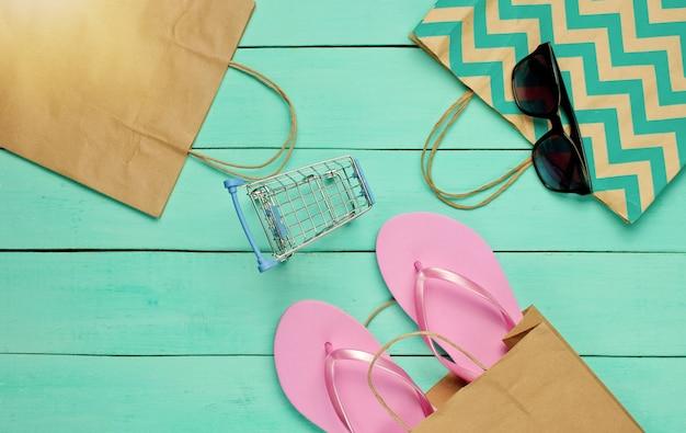 Saldi estivi. concetto di acquisto. accessori estivi da spiaggia (infradito, occhiali da sole), mini carrello della spesa su fondo di legno blu. vista dall'alto. lay piatto