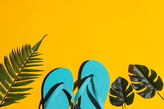 L'estate e il concetto di vacanza infradito palm e foglie di monstera su giallo brillante texture con spazio copia luce dura vista dall'alto laici piatta