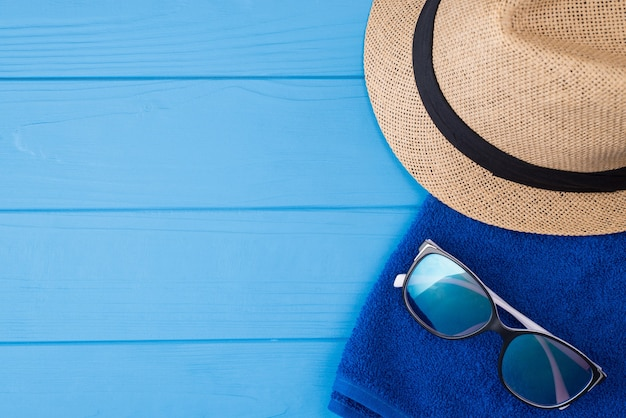 Concetto di vacanza estiva. vista dall'alto sopra la foto ravvicinata di un asciugamano, occhiali da sole e un cappello da sole isolato su sfondo di legno blu con copyspace