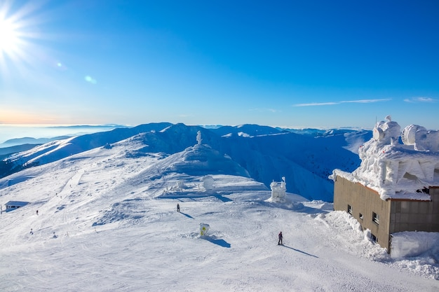 Sole nel cielo azzurro sopra le cime delle montagne invernali. edificio coperto di ghiaccio della stazione di risalita superiore