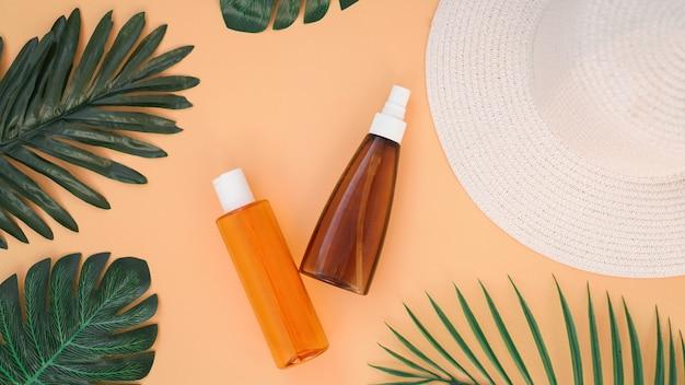 Crema solare, cappello da sole, bottiglia di lozione su sfondo arancione morbido. protezione solare. orario estivo e vacanze