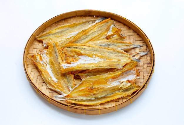 Kingfish nero essiccato al sole in cesto di bambù su sfondo bianco.