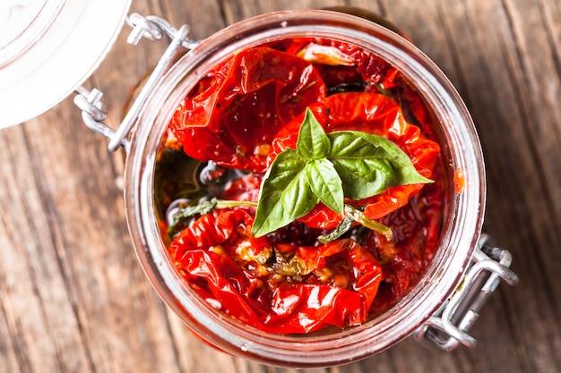 Pomodori secchi in vasetto di vetro con basilico fresco