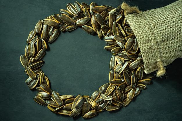 Semi di fiori del sole in un sacchetto di tela. vista dall'alto e copia spazio a forma di cerchio. concetto di agricoltura e fattoria biologica.