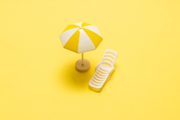 Lettino prendisole e ombrellone giallo su sfondo giallo.