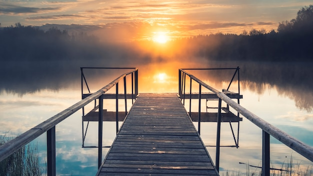 Il sole su un lago nebbioso con un molo di legno nella foresta