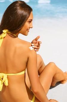 Protezione solare, ragazza che utilizza la protezione solare per proteggere la sua pelle sana. indietro di una ragazza in costume da bagno giallo