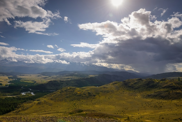 I raggi del sole attraversano enormi nuvole e illuminano meravigliosamente la verde steppa e il fiume tortuoso.