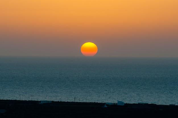 Il sole tramonta dietro la linea dell'orizzonte sul mare.