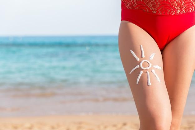 La forma del sole è fatta di crema solare sulla gamba della donna sullo sfondo del mare.