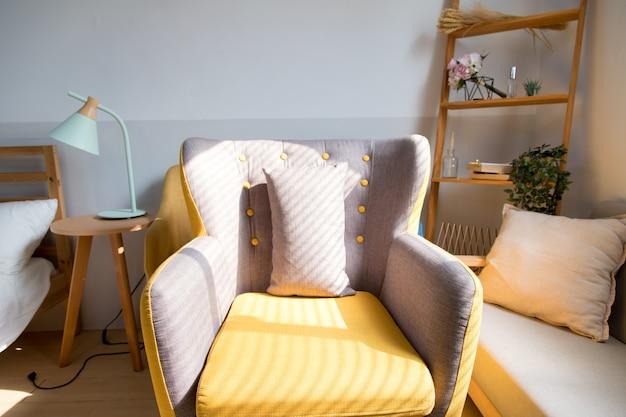 Il sole splende sulla sedia grigio-gialla in soggiorno dalla finestra.
