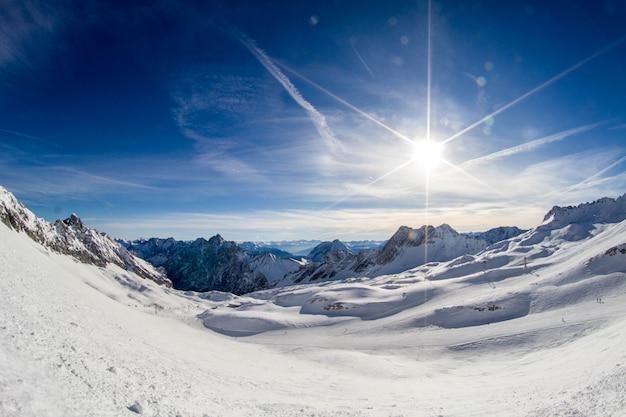 Sole sulla pista da sci e panorama delle alpi innevate dalla stazione sciistica