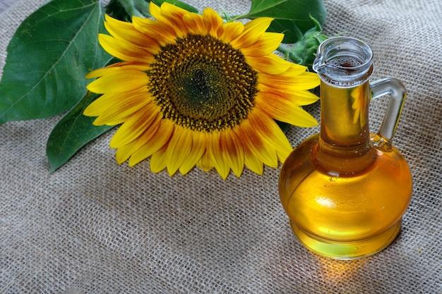 Olio di girasole e un fiore di girasole sul tavolo. olio vegetale naturale.