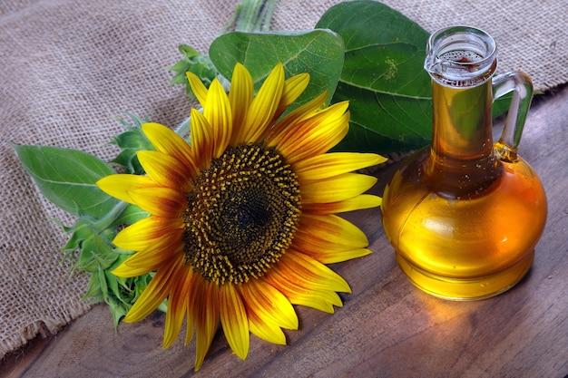 Olio di girasole e un fiore di girasole sul tavolo.